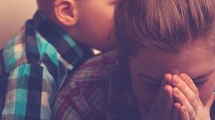 Un enfant étreint sa mère pendant qu'elle pleure.