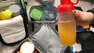 Des boites à lunch et un contenant de jus en avant-plan