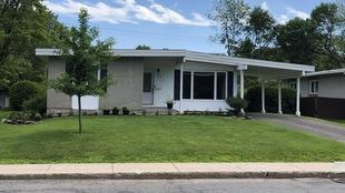 Une maison à un étage faite de brique grise et de vinyle blanc avec une large fenêtre sur la façade et un abri d'auto sur le côté.