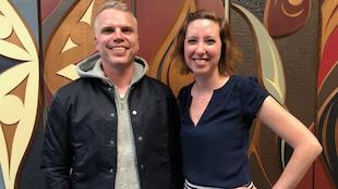un homme et une femme devant un tableau/sculture autochtone