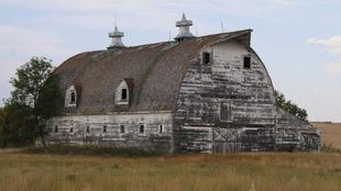 Vue d'une grange abandonnée, seule dans un champ de la Saskatchewan.