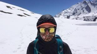 L'athlète au soleil, sur un sommet enneigé porte des lunettes et un masque de haute montage.