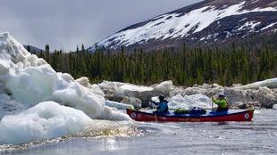 Deux jeunes dans un canot contournent les glaces d'une rivière du Grand Nord.