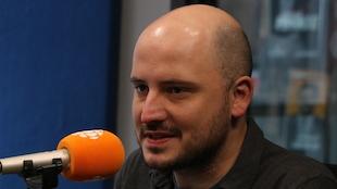 Un homme à la courte barbe et en chandail gris parle au micro.