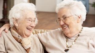Deux femmes âgées souriant en se regardant. L'une enlace l'autre autour des épaules.