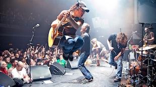 Un guitariste saute dans les airs devant une foule en liesse.