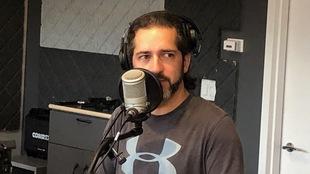 Un homme barbu devant un micro.