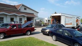 Des voitures et un camion de déménagement sont devant une maison.