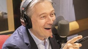 L'homme sourit et regarde Francis Reddy en entrevue.