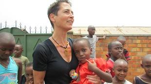 Entourée de jeunes africains, la femmes d'affaires tient un enfant dans ses bras et sourit en regardant le ciel.