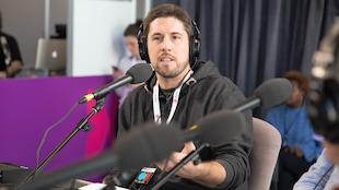 L'auteur est assis derrière un micro et lève le bras gauche en parlant.