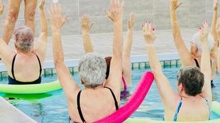 Des femmes à la tête grise qui font des exercices dans une piscine
