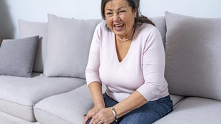 Une femme âgée grimace de douleur en se tenant le genou droit. Elle est assise sur un sofa.