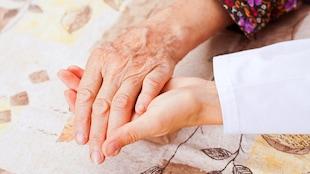 Une femme en fin de vie se fait tenir la main par une personne proche.