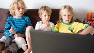 Trois jeunes enfants assis sur un divan regarde l'écran d'un ordinateur portable.