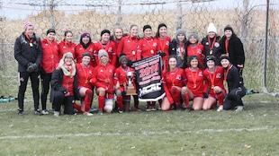 Une photo d'équipe de soccer de jeunes femmes tous habillées en rouge.