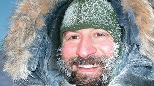 Gros plan du visage d'un homme en habits d'hiver, la barbe, les cils et la tuque recouverts de givre.