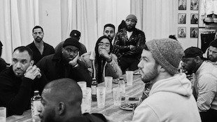 Un groupe d'hommes est assis en rond autour d'une table et écoute attentivement celui qui parle.