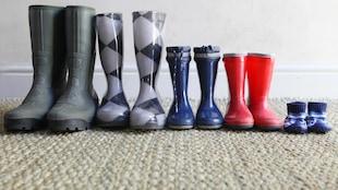 Cinq paires de bottes de pluie, deux d'adultes et trois d'enfants, alignées les unes à côté des autres.