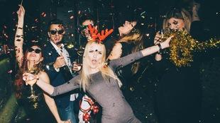 Des gens célèbrent sous les confettis avec un verre d'alcool en main.