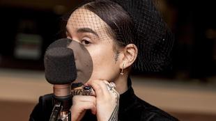 Elle porte un chapeau à filet, des bagues berbères, et une boucle d'oreille en forme de flèche.