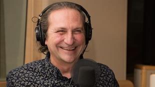 L'animateur Franco Nuovo avec un casque d'écoute sur la tête, dans un studio de radio, avec un large sourire au visage.
