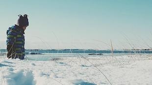 Un petit garçon regarde la plage enneigée à Natashquan.