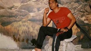 Il porte des sandales blanches, un chandail rouge et un pantalon noir.