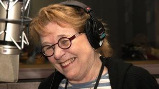 Une femme sourit devant un micro