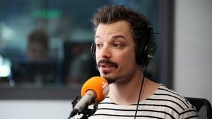Le comédien Guillaume Pépin derrière un micro en studio.