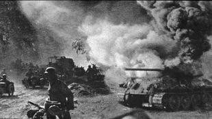 Photo en noir et blanc de soldats qui marchent près d'un tank en feu.