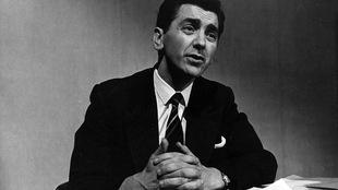 Photo en noir et blanc d'un homme en costume cravate assis sur une table et les mains croisées.