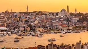 Vue d'Istanbul et de l'estuaire de la Corne d'Or au moment d'un coucher de soleil. Des bateaux traversent le cours d'eau et on peut voir l'église Sainte-Sophie.
