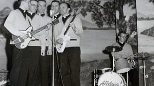 Cinq hommes chantent devant un micro sur pied, deux d'entre eux jouent de la guitare. À droite, un homme joue de la batterie.