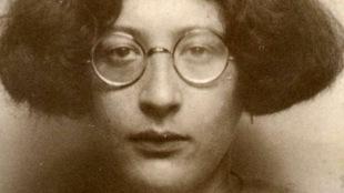 Une femme avec des lunettes rondes regarde la caméra.