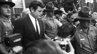 Photo en noir et blanc d'un homme entouré de trois policiers et de plusieurs journalistes munis de caméra.