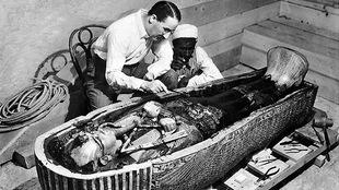 Deux hommes observent attentivement une tombe égyptienne antique.