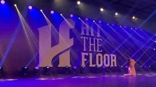 Sur une scène, une jeune participante à l'événement de danse Hit the floor