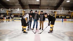 Deux joueurs de hockey sont penchée afin de faire la mise en jeux. La rondelle est sur la glace et Caleb Léveillé est accompagné par son frère Jessie et son cousin Maxime.