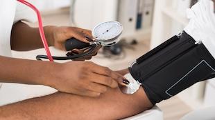 Un membre du personnel médical prend la tension d'un patient sur son bras.