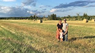 Le couple avec leur jeune fille se retrouve sur un champ, avec des rouleaux de foin en arrière-plan.