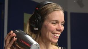 Une femme agite un mélangeur à cocktail devant en souriant.