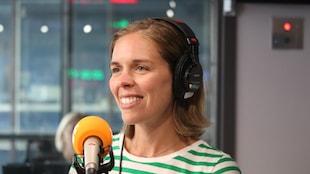 Une femme habillée d'une marinière verte et blanche au micro d'un studio radio.