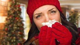 Une femme portant une tuque et des gants rouges se mouche avec un mouchoir devant un sapin.