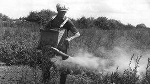 Un homme distribue du DDT.