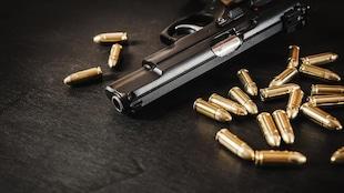 Une arme et plusieurs balles sur une table.