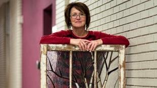 Une dame avec un vitrail en forme de bouleau devant elle.