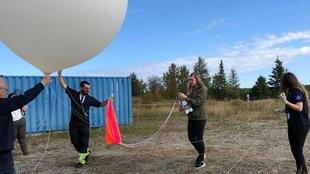 Quatre personnes manipulent un ballon stratosphérique