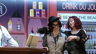 Les deux femmes costumées se donnent la réplique dans un décor de bar.