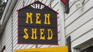 Une affiche en forme de maison sur laquelle il est écrit Men Shed en lettres jaunes.